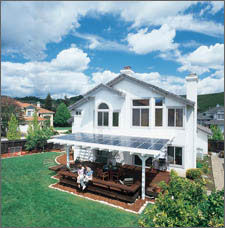 Photo of a home with a solar electric systems integrated into an awning over a back porch.