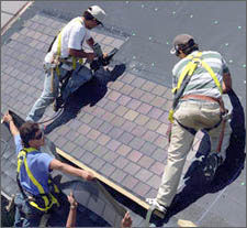 Photo of workers installing PV shingles directly on to a roof.